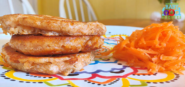 Three Carrot and Coconut Pancakes along with some grated carrot. Your baby will love these tasty, egg-free pancakes